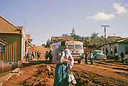 Bus stop in rural settlement on route between Curitiba and Foz do Iguaçu, Laranjeiras do Sol, Paraná state, Brazil in 1962, female tourist passenger in the foreground