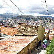 Cholita wrestler Yolanda La Amorosa arrives at her home (left) on the hillside of La Paz with her daughter Adriana after collecting her from school in La Paz, Bolivia. Yolanda is part of the 'Titans of the Ring' wrestling group who perform every  Sunday at El Alto's Multifunctional Centre. Bolivia. The wrestling group includes the fighting Cholitas, a group of Indigenous Female Lucha Libra wrestlers who fight the men as well as each other for just a few dollars appearance money. El Alto, Bolivia, 17th March 2010. Photo Tim Clayton