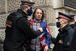 © Licensed to London News Pictures. 04/01/2021. London, UK. A protester is spoken to by police officers attending the JULIAN ASSANGE court case to extradite him to the United States to face espionage charges for publishing US military documents. Photo credit: Ray Tang/LNP