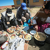 A Bolivian woman on the altiplano cooks a meal of quinoa, potato and llama meat.