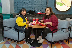 © Licensed to London News Pictures. 20/05/2021. London, UK. Customers with their food orders at the new Jollibee fried chicken flagship restaurant in Leicester Square, West End. Established in 1978, the Filipino fast food company has over 1300 restaurants worldwide. Photo credit: Ray Tang/LNP