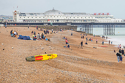 © Licensed to London News Pictures. 27/07/2019. Brighton, UK. Members of the public shelter form the rain as they visit the beach in Brighton and Hove. Photo credit: Hugo Michiels/LNP