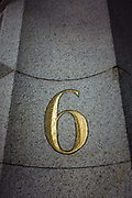 We look up from a low angle at a number six in gold colour, in a doorway of offices in the City of London. The 6 is set in granite at this prestigious address in the City of London, the capital's financial heart.