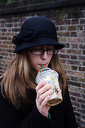 A 15 year-old teenage girl sips a Starbucks Frapuccino coffee through a straw in a London Street.