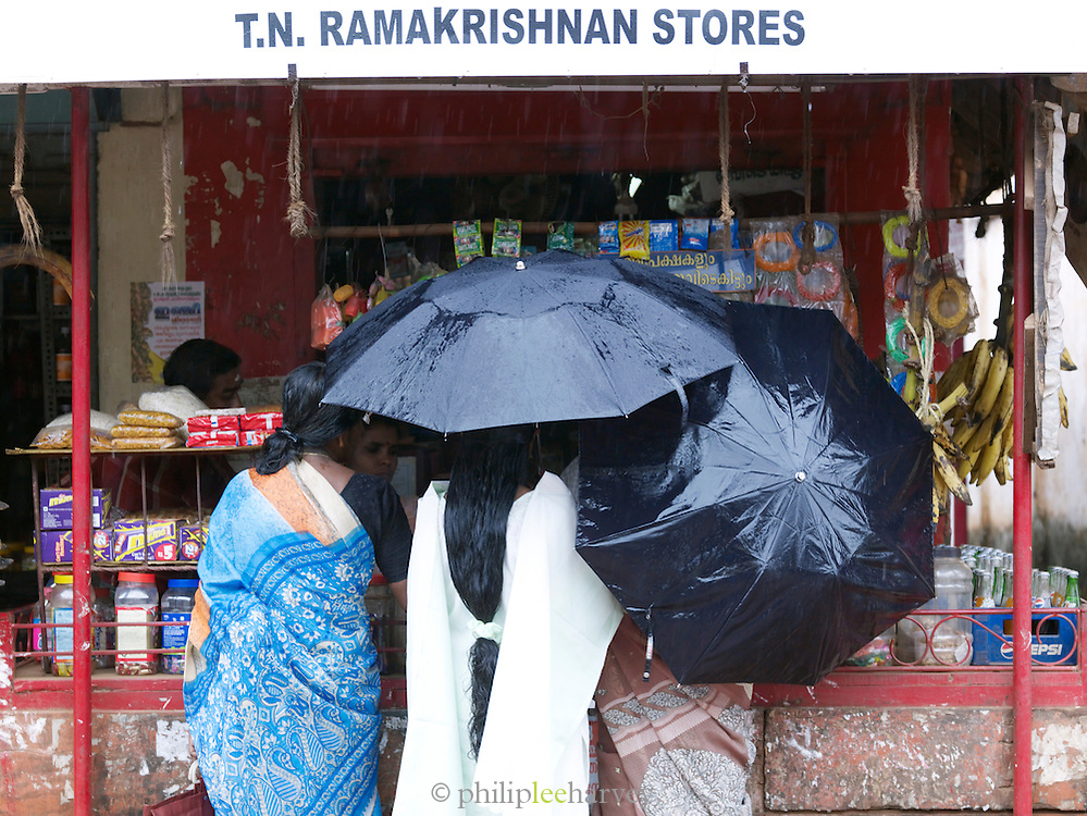 Three women shopping whilst sheltering under umbrellas, Cochin, Kerala, India