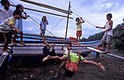 Young children play on a banka, a fishing boat at low tide in Gumacas bay. The children entertain themselves with whatever they can get their hands on, given that no one has toys in their village, Aurora Province, Philippines