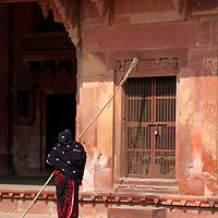 Asia, India, Fatehpur Sikri. woman sweeping facade at Fatehpur Sikri.