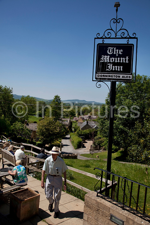 The Mount Inn at Stanton looking out over the landscape of The Cotswolds, Gloucestershire, UK.  Popular with both the English themselves and international visitors from all over the world, the area is well known for gentle hillsides 'wolds', outstanding countryside, sleepy ancient limestone villages, historic market towns and for being so 'typically English' where time has stood still for over 300 years. Throughout the Cotswolds stone features in buildings and stone walls act as a common thread in seamlessly blending the historic towns & villages with their surrounding landscape. One of the most 'quintessentially English' and unspoiled regions of England.