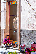 An indigenous woman weaves hats out of wool on a street corner in the historic center of Guanajuato City, Guanajuato, Mexico.