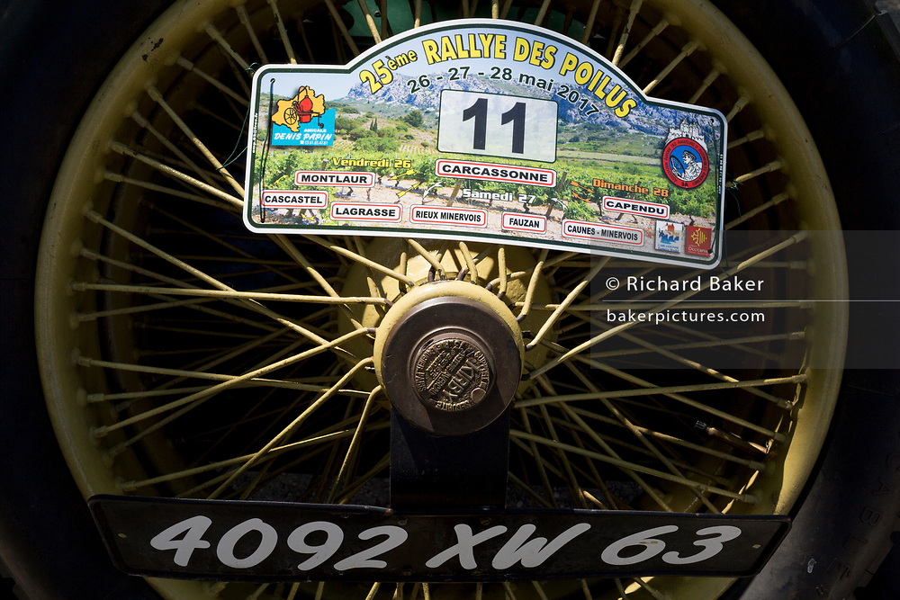 Detail of a rear wheel from a visiting vintage car in the centre of a French village, during a three-day rally journey through the Corbieres wine region, on 26th May, 2017, in Lagrasse, Languedoc-Rousillon, south of France. Lagrasse is listed as one of France's most beautiful villages and lies on the famous Route 20 wine route in the Basses-Corbieres region dating to the 13th century.