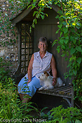 Back Garden - Shirley with Daisy sitting on an arbour seat by the pond. Clover Cottage