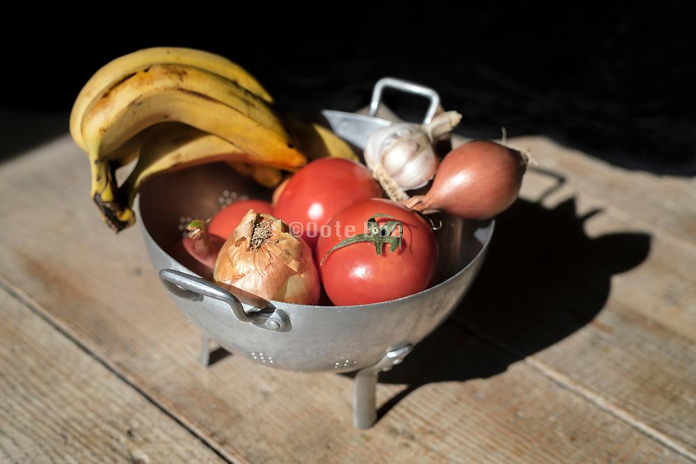 still life with banana's onions garlic and tomatos