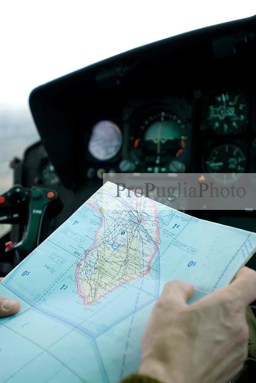Puglia, a pilot of the italian Coast Guard reading the map of  souther Italy.