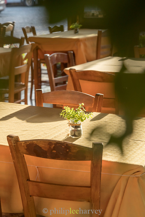 Old wooden chairs and tables of sidewalk cafe on sunny day, Avgonyma, Chios, Greece