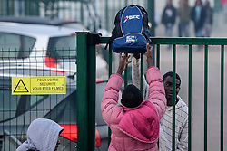 © Licensed to London News Pictures. 25/10/2016. Calais, France.  Migrants due to leave the camp pass bags over a secure fence in the migrant and refugee camp in Calais, known as the 'Jungle'. French authorities have moved thousands of refugees and migrants living at the makeshift living area on the French coast, with some still refusing to leave. . Photo credit: Ben Cawthra/LNP