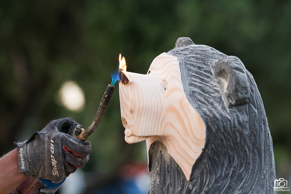 Darin Finnigan torches a wooden black bear sculpture to add color after Ray Schulz sculpts the log with a chainsaw.  Schulz visited Black Bear Diner in Milpitas, Calif. on July 11, 2012 to demonstrate the chainsaw carving process of wooden statues found at every diner.  Photo by Stan Olszewski/SOSKIphoto.