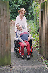 Carer pushing man with Cerebral Palsy in wheelchair through park gate,