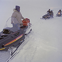 BAFFIN ISLAND, NUNAVUT, CANADA. Inuit guides tie snomobiles together to tow heavy load up hill en route to Great Sail Peak expedition.