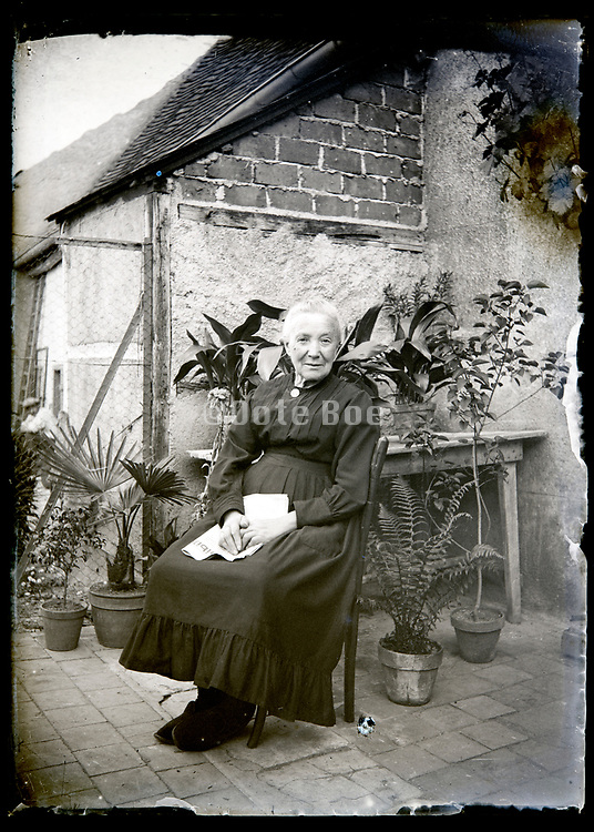 content elderly woman sitting in backyard France circa 1920s