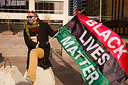 02 APRIL 2021 - MINNEAPOLIS, MINNESOTA: EVAN PUGH waves a Black Lives Matter flag on the plaza across the street from the Hennepin County Courthouse. Protesters are keeping a 24 hour presence in front of the Hennepin County Courthouse in Minneapolis during the murder trial of former Minneapolis Police Officer Derek Chauvin. Chauvin is on trial for murdering George Floyd in 2020. Floyd's death, while restrained and in police custody, set off a summer of racial justice protests across the United States.      PHOTO BY JACK KURTZ