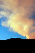Smoke and steam irrupting from the Southern slopes of Mount Etna, The highest and most active volcano in Europe, at sun set, Nicolosi, Sicily, Italy July 2006