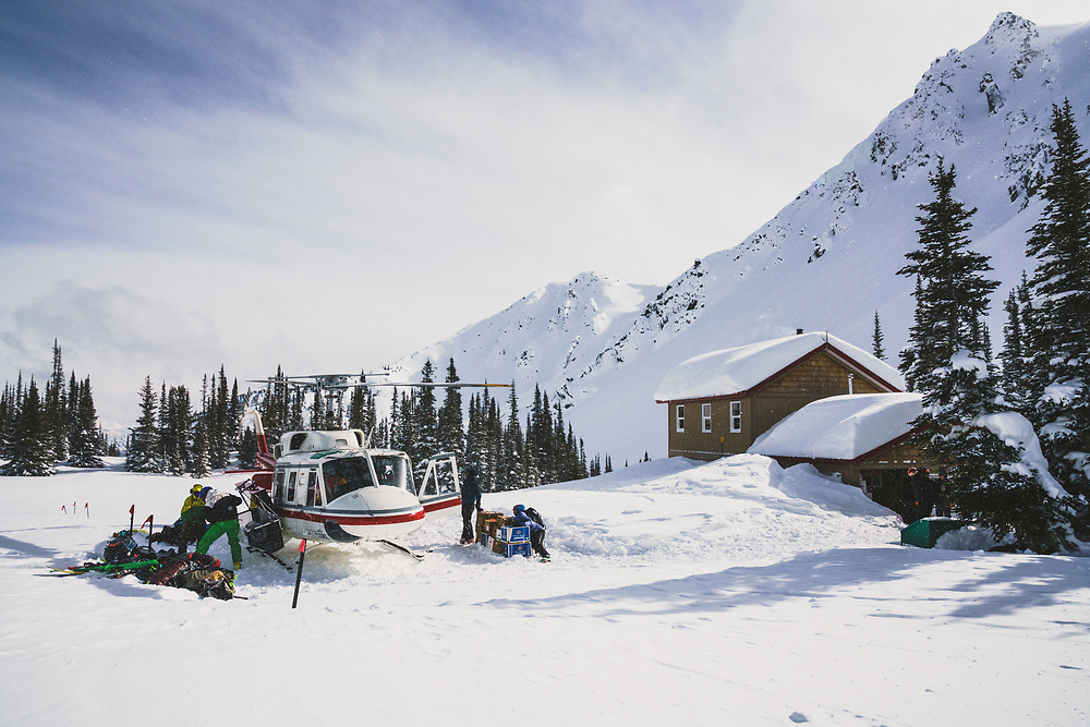 A group of backcountry skiers offloads a helicopter at the beginning of their seven day stay at the Meadow Hut, Esplanade Range, British Columbia, Cananda.