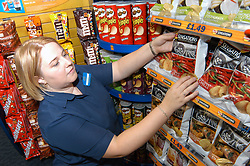 Young woman working in Blockbuster video rental shop arranging display of crisps for sale; Merseyside