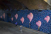 People interact with a mural at Borough Market which serves as a personal dedication and homage to the terror attack at London Bridge by graffiti artist Jimmy C, on 4th April 2017 in London, United Kingdom. The heart shapes, which are a regular fixture of the artist's work are a call to respond with love not fear. While the piece is not specifically designed as a memorial to those who died on June 3rd 2017, it is already being taken into people's hearts where the attacks took place, and seems inevitable to become a focus for remembrance and commemorations in the future.