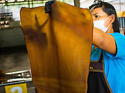 """16 DECEMBER 2014 - CHUM SAENG, RAYONG, THAILAND: A worker hangs rubber sheets to dry before they are put into a smoker at a large rubber plantation near Chum Saeng, Thailand. Thailand is the second leading rubber exporter in the world. In the last two years, the price paid to rubber farmers has plunged from approximately 190 Baht per kilo (about $6.10 US) to 45 Baht per kilo (about $1.20 US). It costs about 65 Baht per kilo to produce rubber ($2.05 US). Prices have plunged 5 percent since September, when rubber was about 52Baht per kilo. Some rubber farmers have taken jobs in the construction trade or in Bangkok to provide for their families during the slump. The Thai government recently announced a """"Rubber Fund"""" to assist small farm owners but said prices won't rebound until production is cut and world demand for rubber picks up.    PHOTO BY JACK KURTZ4 as about 52Baht per kilo. Some rubber farmers have taken jobs in the construction trade or in Bangkok to provide for their families during the slump. The Thai government recently announced a """"Rubber Fund"""" to assist small farm owners but said prices won't rebound until production is cut and world demand for rubber picks up.    PHOTO BY JACK KURTZ"""