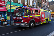 A London Fire Brigade fire engine drives to an emergency on Stoke Newington high street, London, United Kingdom.