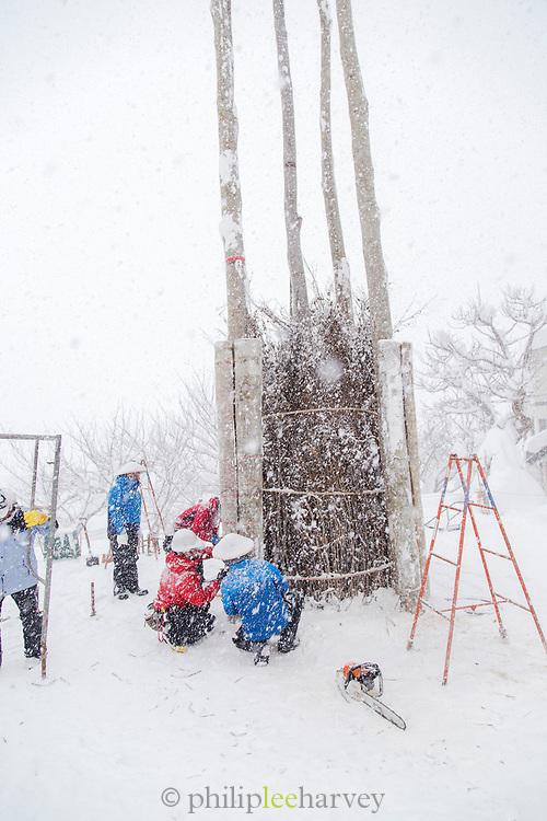 Group of people preparing bonfire in snow, Nozawaonsen, Japan