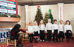 Students from the Inter Lakes Elementary School Kinderchoir sing a Christmas carole to open Wednesday evening's session of the annual Children's Christmas Auction.  (Alan MacRae/for the Laconia Daily Sun)