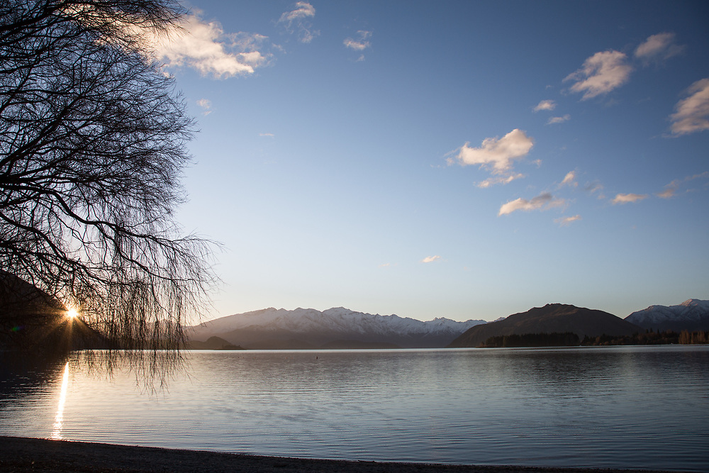Bare winter trees frame Lake Wanaka in the late late afternoon winter light.