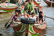 17 JUNE 2013 - YANGON, MYANMAR:  A boat full of commuters pulls away from jetty on the Yangon side of the Yangon River in Yangon. Many working class Burmese live on the far side of the river and the boats to commute to and from work every day.   PHOTO BY JACK KURTZ