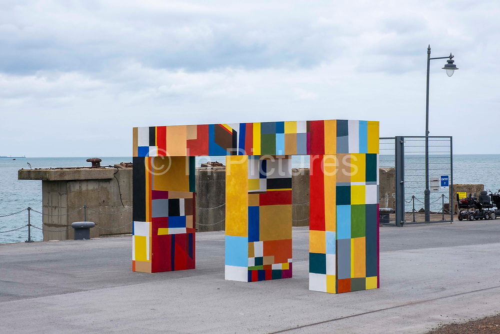 Gateways of the sea by artist Atta Kwami on 15th of July 2021, in Folkestone, United Kingdom. The free standing three-dimensional artworks are an imposing but joyful asymmetric double archway stands at the junction of four pathways in the centre of the Harbour Arm. The artwork is part of the Creative Folkestone Triennial 2020, The Plot, which sees 27 newly commissioned artworks appearing around the south coast seaside town. The new work builds on the work from previous triennials making Folkestone the biggest urban outdoor contemporary art exhibition in the UK.