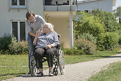 Son walking with disabled mother on wheelchair, Bavaria, Germany