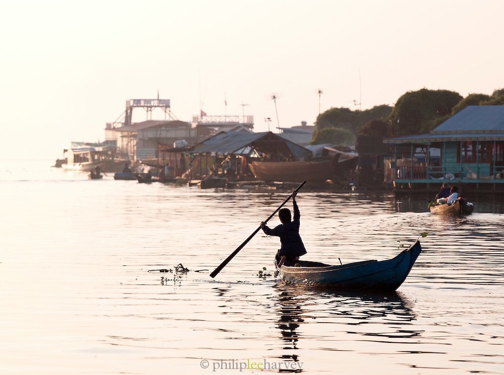 A small boat paddled though one of the floating villages on the great Tonlé Sap lake, Cambodia