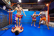 23 DECEMBER 2014 - BANGKOK, THAILAND: A boxer helps another fighter get kinks out of his back while other boxers spar in the ring at the Kanisorn gym in Bangkok. The Kanisorn boxing gym is a small gym along the Wong Wian Yai - Samut Sakhon train tracks. Young people from the nearby communities come to the gym to learn Thai boxing. Muay Thai (Muai Thai) is a mixed martial art developed in Thailand. Muay Thai became widespread internationally in the twentieth century, when Thai boxers defeated other well known boxers. A professional league is governed by the World Muay Thai Council. Muay Thai is frequently seen as a way out of poverty for young Thais. Muay Thai professionals and champions are often celebrities in Thailand.     PHOTO BY JACK KURTZ