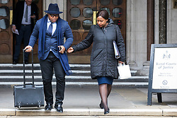 © Licensed to London News Pictures. 23/02/2018. London, UK. Takesha Thomas (R) reaches for the hand of her husband, Lanre Haastrup (L), as they leave the High Court in London after judges ruled that doctors at King's College Hospital can withdraw life support for their son, Isaiah Haastrup, who has suffered severe brain damage. Photo credit: Rob Pinney/LNP