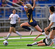 OFallon midfielder Avery Taake leaps over Edwardsville defender Ulla Sharp. OFallon defeated Edwardsville in a girls soccer playoff game at OFallon High School in OFallon, IL on Tuesday June 8, 2021. <br /> Tim Vizer/Special to STLhighschoolsports.com.