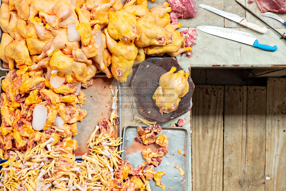 View looking down on a butcher shop with freshly cut pieces of poultry in the vast Mercado Hidalgo, a public market inside a former train station in the historic center of Guanajuato City, Guanajuato, Mexico.