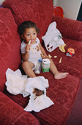 Neglected toddler sitting on sofa eating bread surrounded by dirty nappies and rubbish,