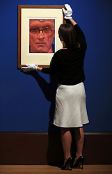 An employee of the Royal Collection Trust adjusts David Hockney's Self-Portrait, which is on display in the Portrait of the Artist exhibition at the Queen's Gallery, Buckingham Palace, London.