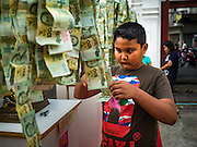 24 NOVEMBER 2015 - BANGKOK, THAILAND: A boy staples 20 Baht notes (about .60¢ US) to a chain of donations at the Wat Saket temple fair. Wat Saket is on a man-made hill in the historic section of Bangkok. The temple has golden spire that is 260 feet high which was the highest point in Bangkok for more than 100 years. The temple construction began in the 1800s in the reign of King Rama III and was completed in the reign of King Rama IV. The annual temple fair is held on the 12th lunar month, for nine days around the November full moon. During the fair a red cloth (reminiscent of a monk's robe) is placed around the Golden Mount while the temple grounds hosts Thai traditional theatre, food stalls and traditional shows.       PHOTO BY JACK KURTZ