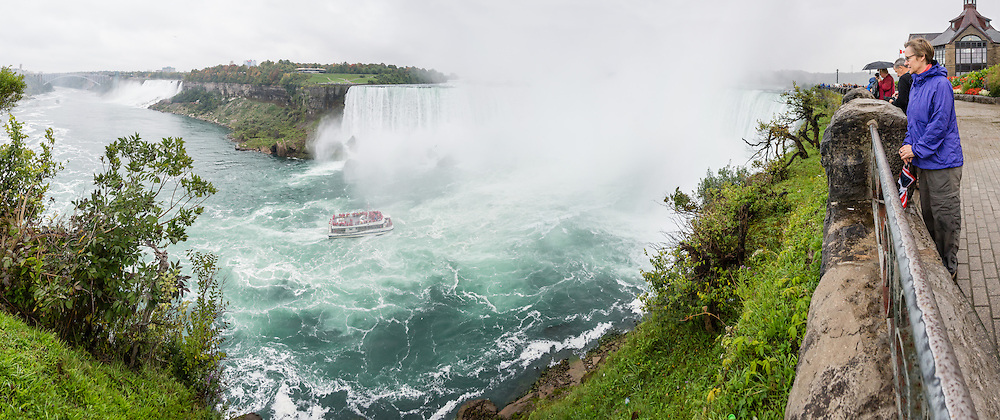 The town of Niagara Falls in Ontario, Canada, gives excellent views of all three sections of Niagara Falls, which drops 167 feet (51 m). Niagara Falls has the highest flow rate of any waterfall in the world. Niagara Falls is the name for the combined flow of Horseshoe Falls, American Falls and Bridal Veil Falls, on the Niagara River along the international border between Ontario, Canada and New York, USA. The Niagara River drains Lake Erie into Lake Ontario. Horseshoe Falls is the most powerful waterfall in North America, as measured by vertical height combined with flow rate. The falls are 17 miles north-northwest of Buffalo, New York and 75 miles south-southeast of Toronto. The panorama was stitched from 9 overlapping photos.
