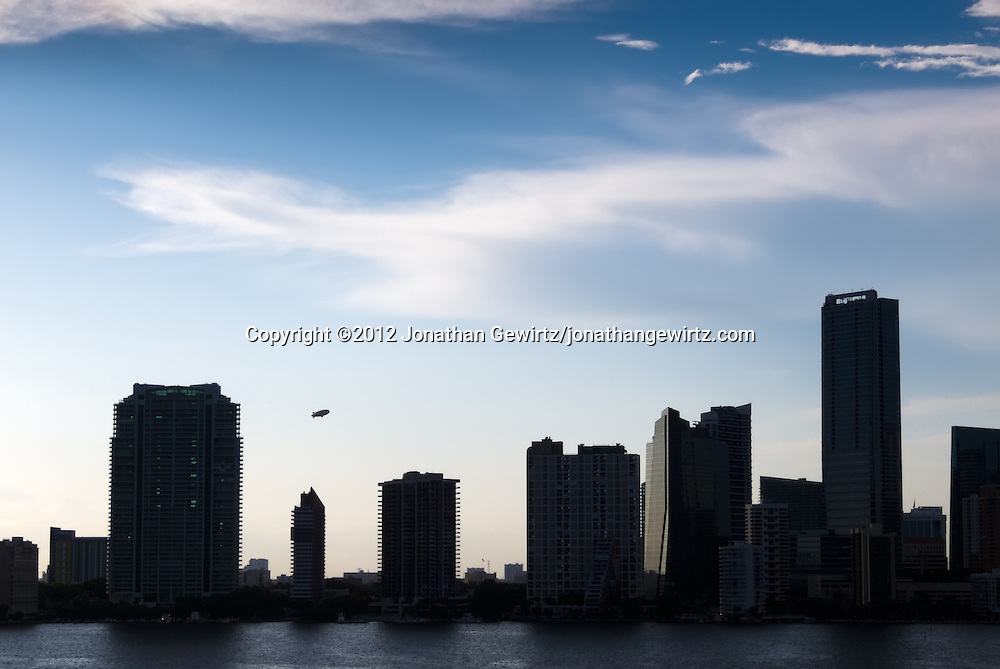 A Goodyear blimp climbs in the late-afternoon sky behind silhouetted condominium and office buildings on Miami's Brickell Avenue. WATERMARKS WILL NOT APPEAR ON PRINTS OR LICENSED IMAGES.