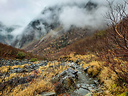 """Fog in Yokoo-hontani Valley. Kamikochi (""""Upper Highlands"""") is a high valley within the Hida Mountains, in Chubu-Sangaku National Park, Nagano Prefecture, Japan. Last logged in the mid 1800s, it is now a popular nature resort. Embraced within the """"Northern Alps"""" of the Japanese Alps, the valley floor ranges from 1400 m (4600 ft) to 1600 m (5200 ft) elevation. Its highest peak is Okuhotakadake (3190 m or 10,470 ft)."""