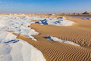 Wind sculpted chalk waves and sand in the Sahara Beida (White Desert) near Farafra, Egypt