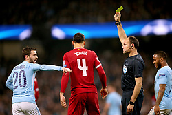 Manchester City's Bernardo Silva (left) receives a yellow card from Referee Antonio Miguel Mateu Lahoz for unsporting behaviour