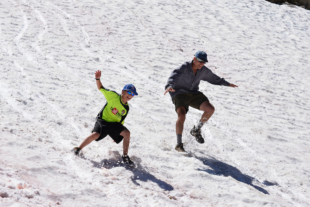 Father and son glissading down a snowfield high in the Wallowa Mountains of Oregon.